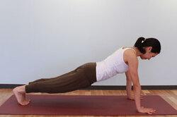 <span>5.</span>呼吸を止めて、もう一方の脚を後ろへ引き、両手と足の爪先で体重を支える。頭と胴を一直線に保ち(腕立て伏せの体勢)、両手の間の床一点を見る。